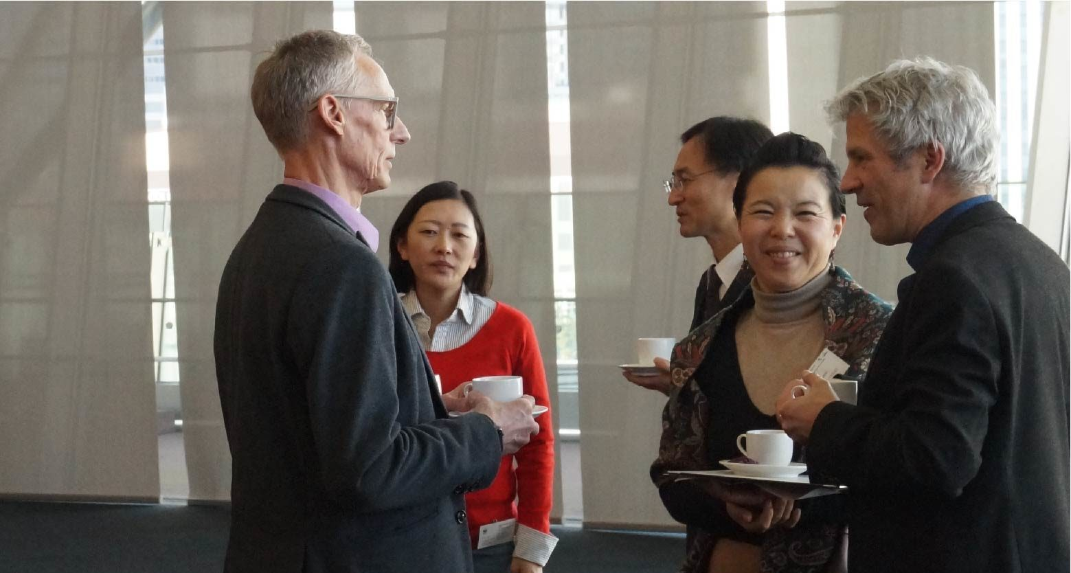 Five people are to be seen. One of them is a speaker of the symposium. He is holding a businesscard. The other people are holding cups of coffee and one woman next to the speaker is smyling towards the viewer